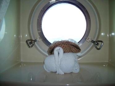 A towel animal shaped like a turkey, wearing a hat.