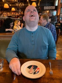 Paul laughing at his George H.W. plate at St. Anselm in Washington, D.C.