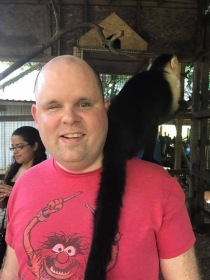 Paul with a monkey on his shoulder in Roatan.