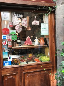 Florentine steaks hanging on hooks in a window in Florence, Italy