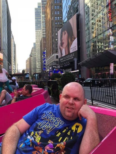 A picture of Paul reclined on a lounger in Times Square in New York City