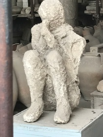 A preserved statue of a scared man in the ruins of Pompeii