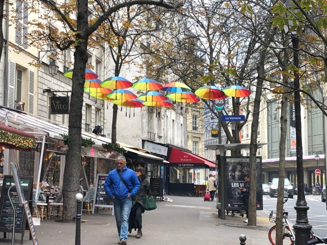 A number of colorful umbrellas along a street in the Marais neighborhood of Paris