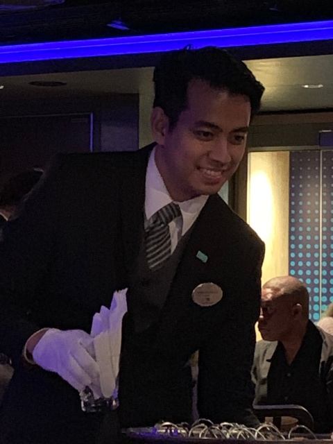 Our butler Joseph serves us canapes at the Haven staff meet and greet on the Norwegian Getaway cruise ship.